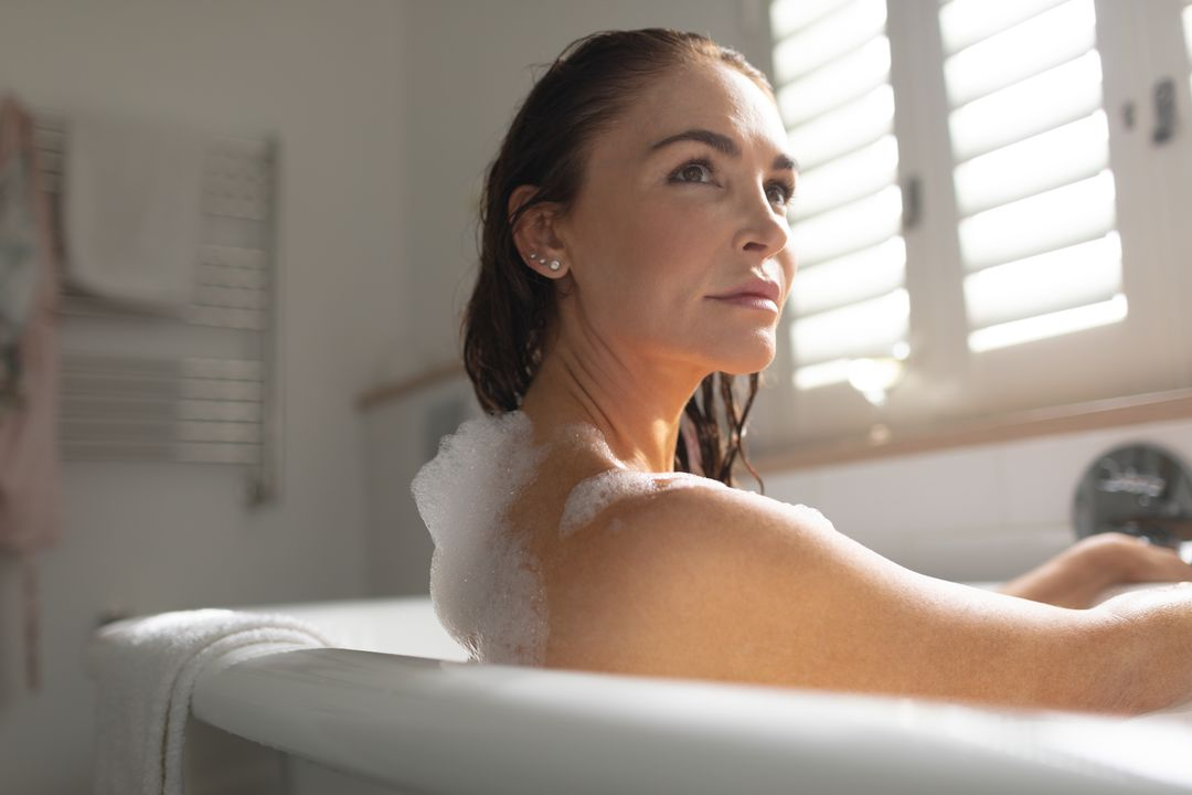 Thoughtful beautiful woman taking bubble bath in bathroom at home