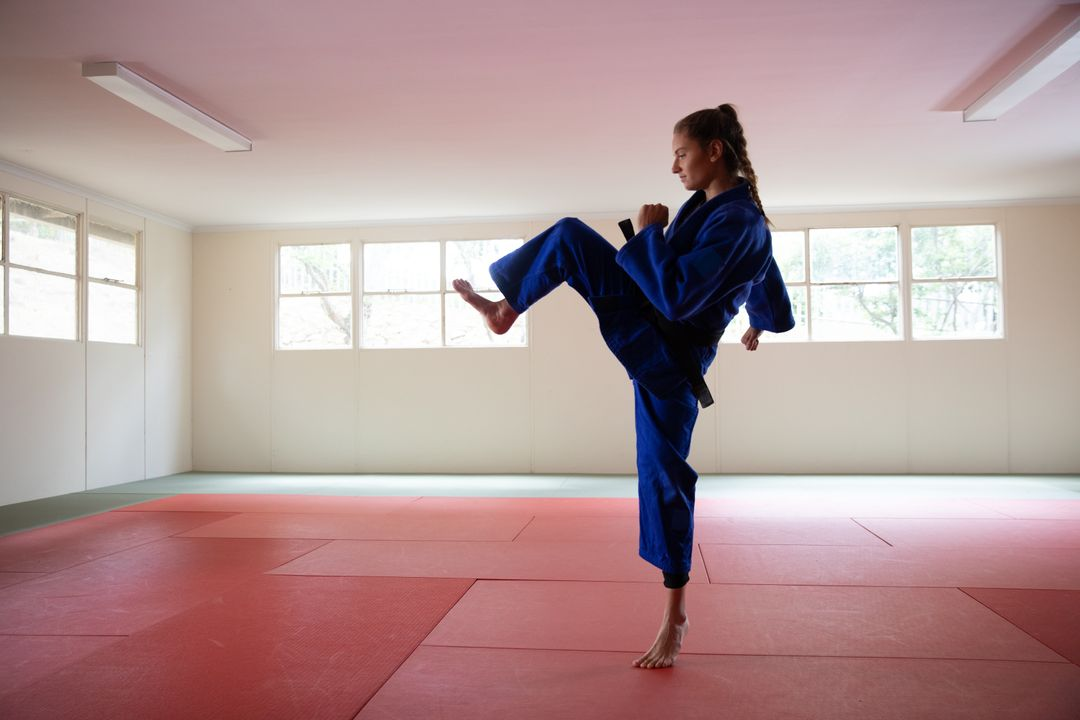 Caucasian female judoka wearing blue judogi, standing on a mat and warming up while preparing for her judo training in a bright studio. Free Stock Images from PikWizard