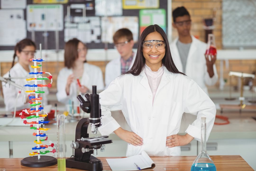 Portrait of school girl standing with hand on hip in laboratory at school Free Stock Images from PikWizard