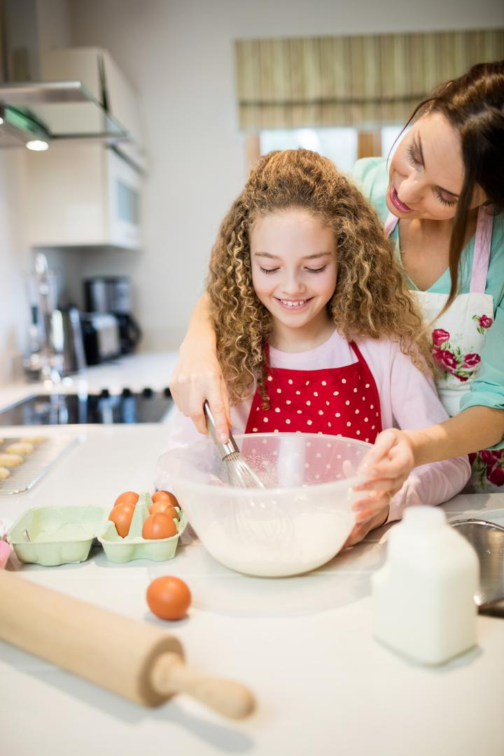 Mother assisting daughter in whisking flour in kitchen at home