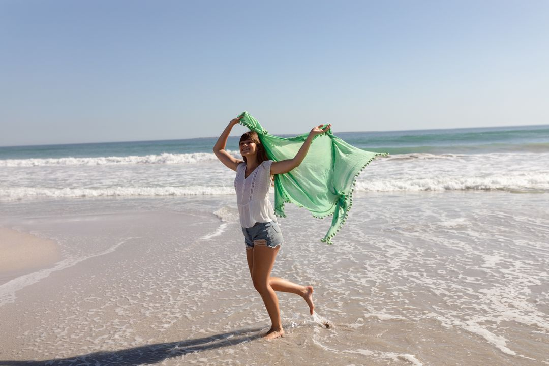Beautiful young woman waving scarf on beach in the sunshine
