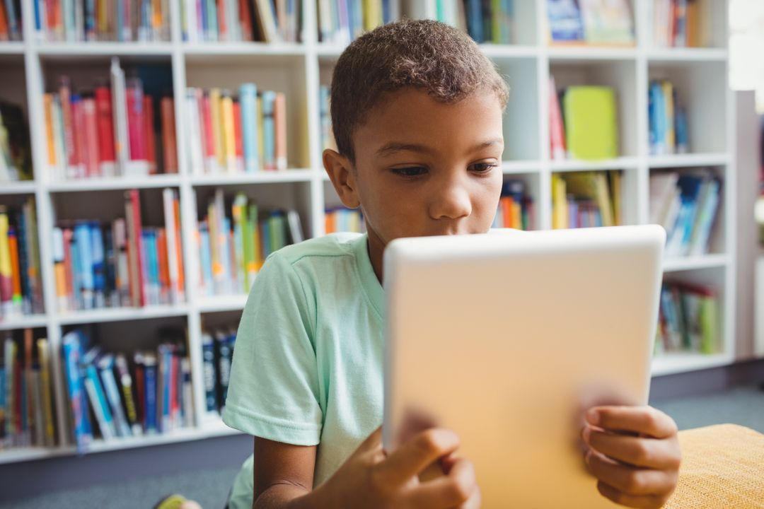 Little boy using a tablet in the library Free Stock Images from PikWizard