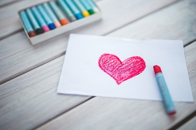 Sheet of paper with pink crayon and love heart drawing