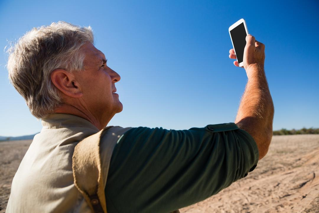 Man photographing from mobile phone against blue sky on landscape Free Stock Images from PikWizard