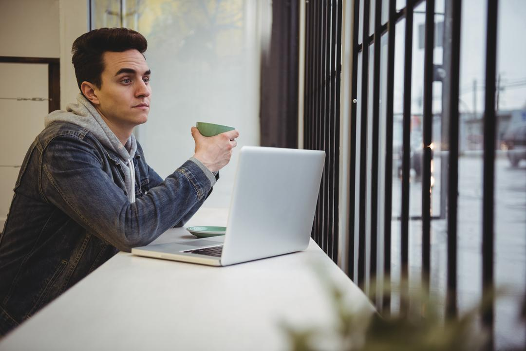 Thoughtful man holding cup of coffee in coffee shop