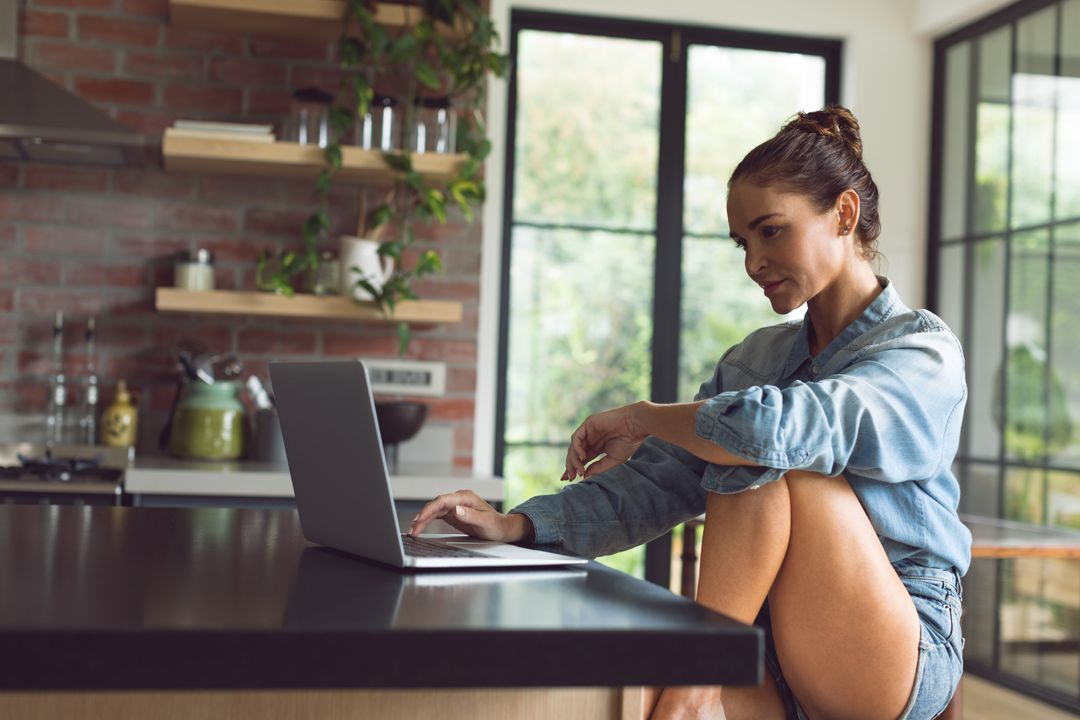 Beautiful woman using laptop on worktop in kitchen at comfortable home