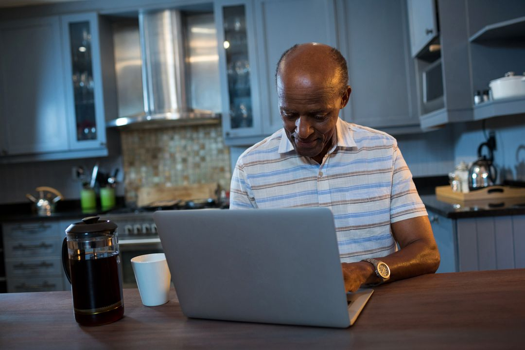 Senior man using laptop at table in kitchen at home
