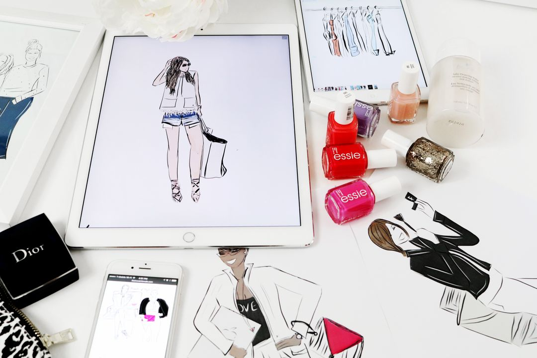 Tablet with fashion drawing on a table surrounded by nailpolish and graphics