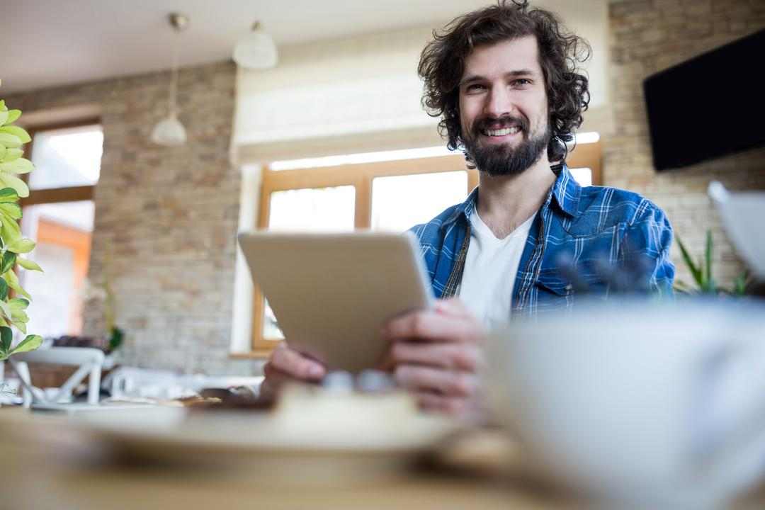 Portrait of smiling man using digital tablet in coffee shop Free Stock Images from PikWizard