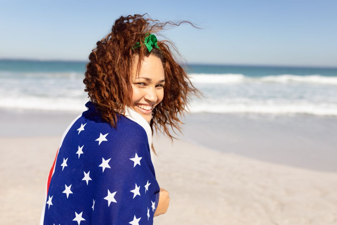 Rear view of beautiful happy young Mixed-race woman wrapped in american flag looking at camera on beach in the sunshine
