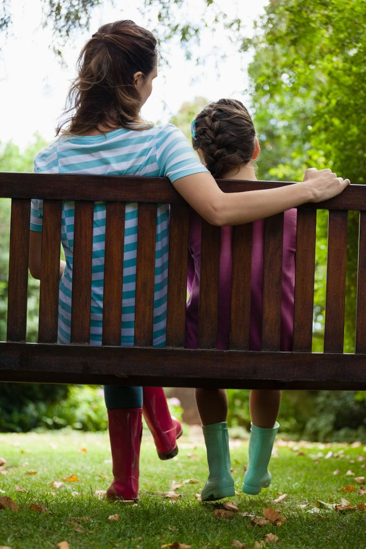 Rear view of girl and woman sitting on wooden bench at backyard Free Stock Images from PikWizard
