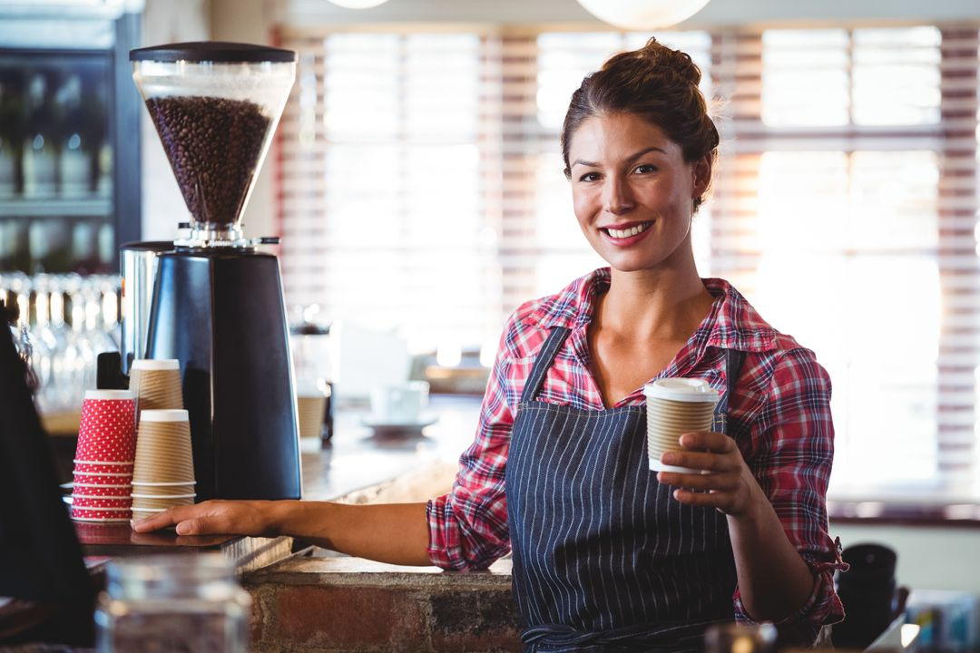 Waitress holding a cup of coffee in a cafe Free Stock Images from PikWizard