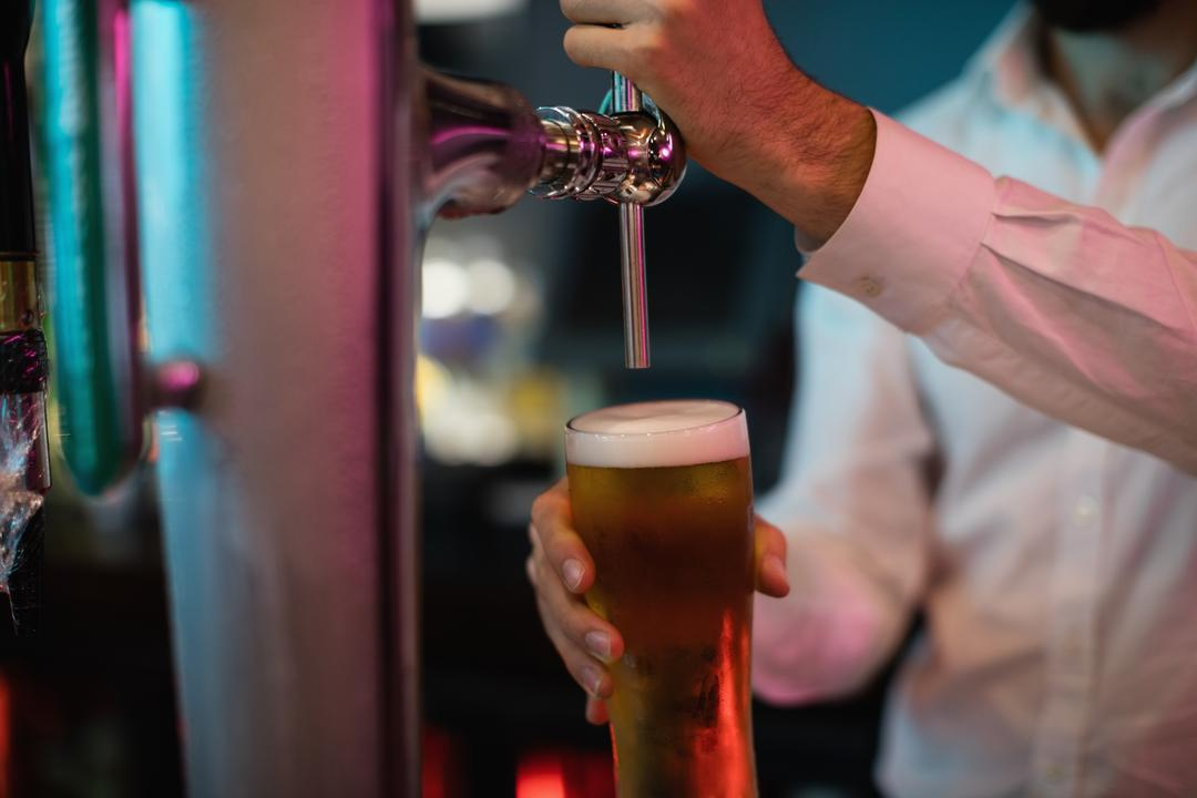 Close-up of bartender filling beer from bar pump at bar counter