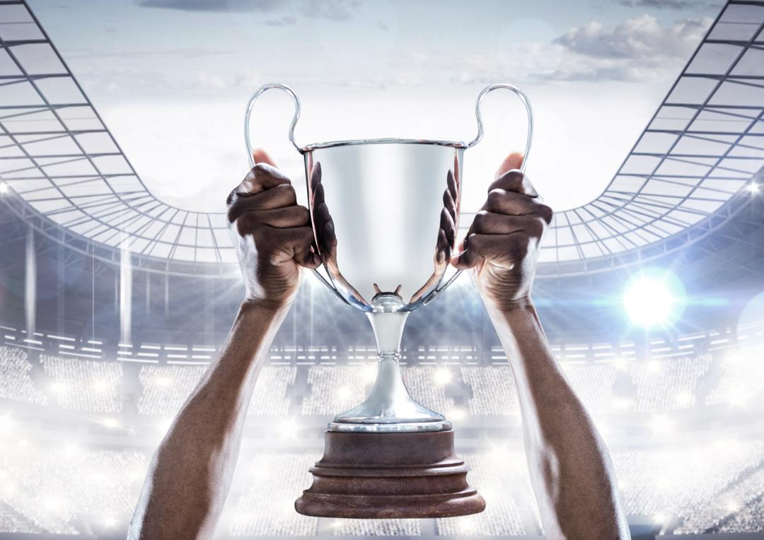 Digital composition of hands holding a champion trophy in stadium