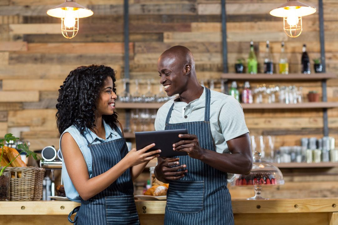 Smiling waiter and waitress using digital tablet at counter in cafe Free Stock Images from PikWizard