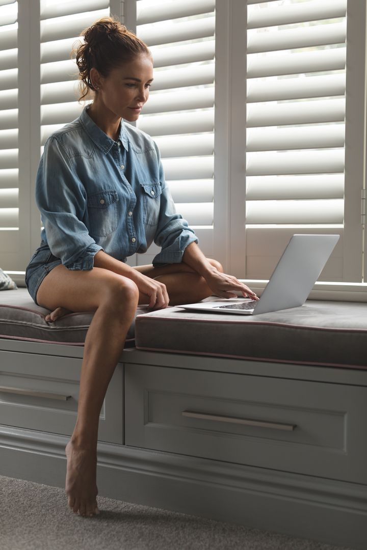 Beautiful woman using laptop while sitting on window seat in a comfortable home