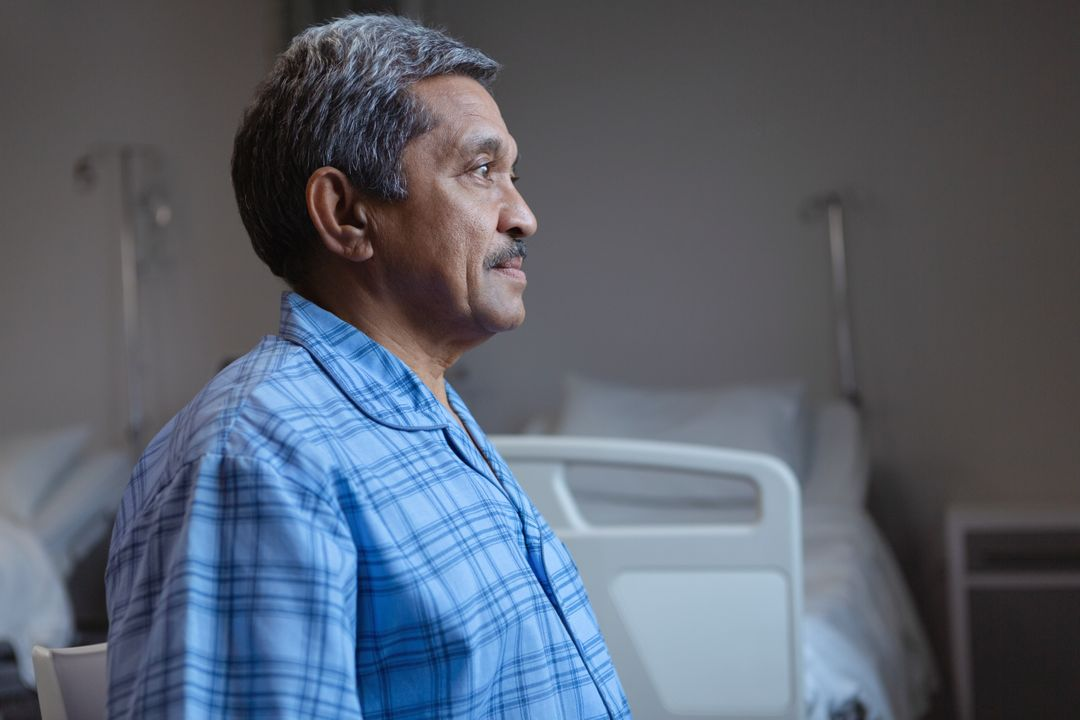 Side view of mature male patient sitting on medical bed and looking away in medical ward at hospital
