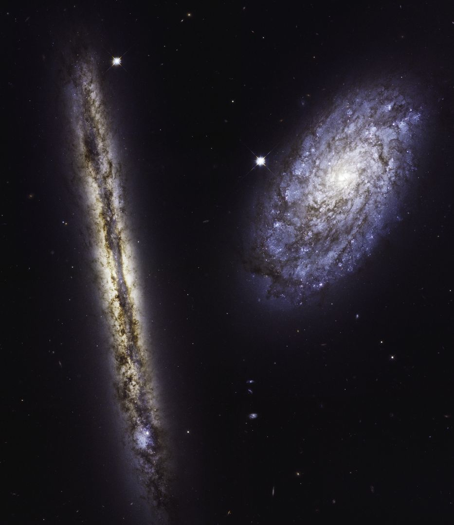 "In celebration of the 27th anniversary of the launch of NASA's Hubble Space Telescope on April 24, 1990, astronomers used the legendary telescope to take a portrait of a stunning pair of spiral galaxies. This starry pair offers a glimpse of what our Milky Way galaxy would look like to an outside observer.  The edge-on galaxy is called NGC 4302, and the tilted galaxy is NGC 4298. These galaxies look quite different because we see them angled at different positions on the sky. They are actually very similar in terms of their structure and contents.  From our view on Earth, researchers report an inclination of 90 degrees for NGC 4302, which is exactly edge on. NGC 4298 is tilted 70 degrees.  In NGC 4298, the telltale, pinwheel-like structure is visible, but it's not as prominent as in some other spiral galaxies. In the edge-on NGC 4302, dust in the disk is silhouetted against rich lanes of stars. Absorption by dust makes the galaxy appear darker and redder than its companion. A large blue patch appears to be a giant region of recent star formation.  Read more: <a href=""https://go.nasa.gov/2pGyA4o"" rel=""nofollow"">go.nasa.gov/2pGyA4o</a>  <b><a href=""http://www.nasa.gov/audience/formedia/features/MP_Photo_Guidelines.html"" rel=""nofollow"">NASA image use policy.</a></b>  <b><a href=""http://www.nasa.gov/centers/goddard/home/index.html"" rel=""nofollow"">NASA Goddard Space Flight Center</a></b> enables NASA's mission through four scientific endeavors: Earth Science, Heliophysics, Solar System Exploration, and Astrophysics. Goddard plays a leading role in NASA's accomplishments by contributing compelling scientific knowledge to advance the Agency's mission.  <b>Follow us on <a href=""http://twitter.com/NASAGoddardPix"" rel=""nofollow"">Twitter</a></b>  <b>Like us on <a href=""http://www.facebook.com/pages/Greenbelt-MD/NASA-Goddard/395013845897?ref=tsd"" rel=""nofollow"">Facebook</a></b>  <b>Find us on <a href=""http://instagrid.me/nasagoddard/?vm=grid"" rel=""nofollow"">Instagram</a></b>     Free Stock Images from PikWizard"