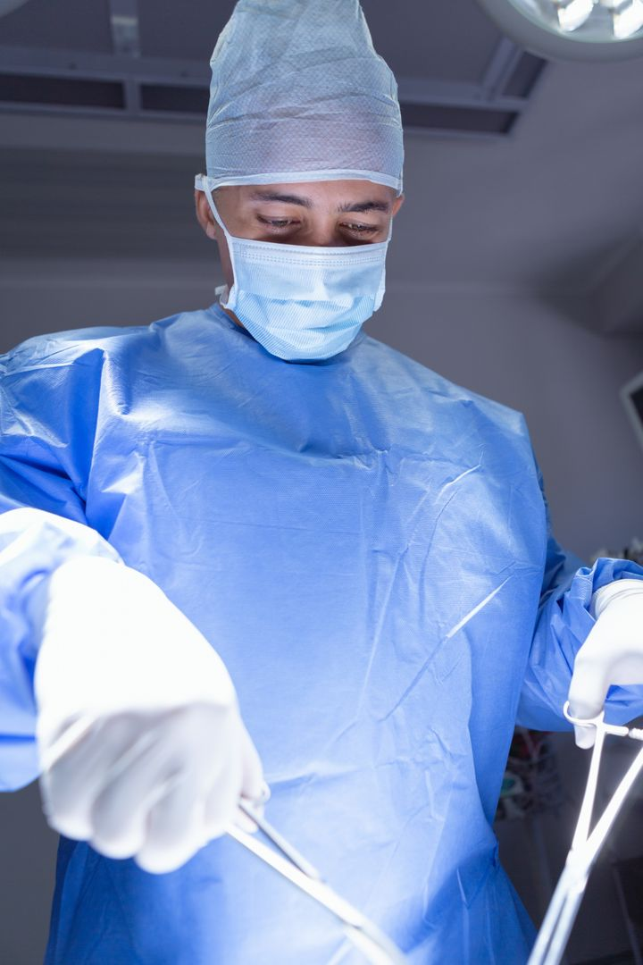 Low angle view of male surgeon performing surgery operation room at hospital Free Stock Images from PikWizard