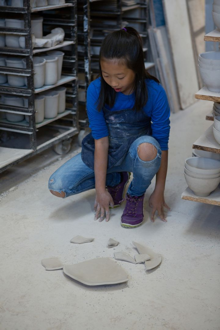 Girl looking at broken pieces of plate in pottery workshop Free Stock Images from PikWizard
