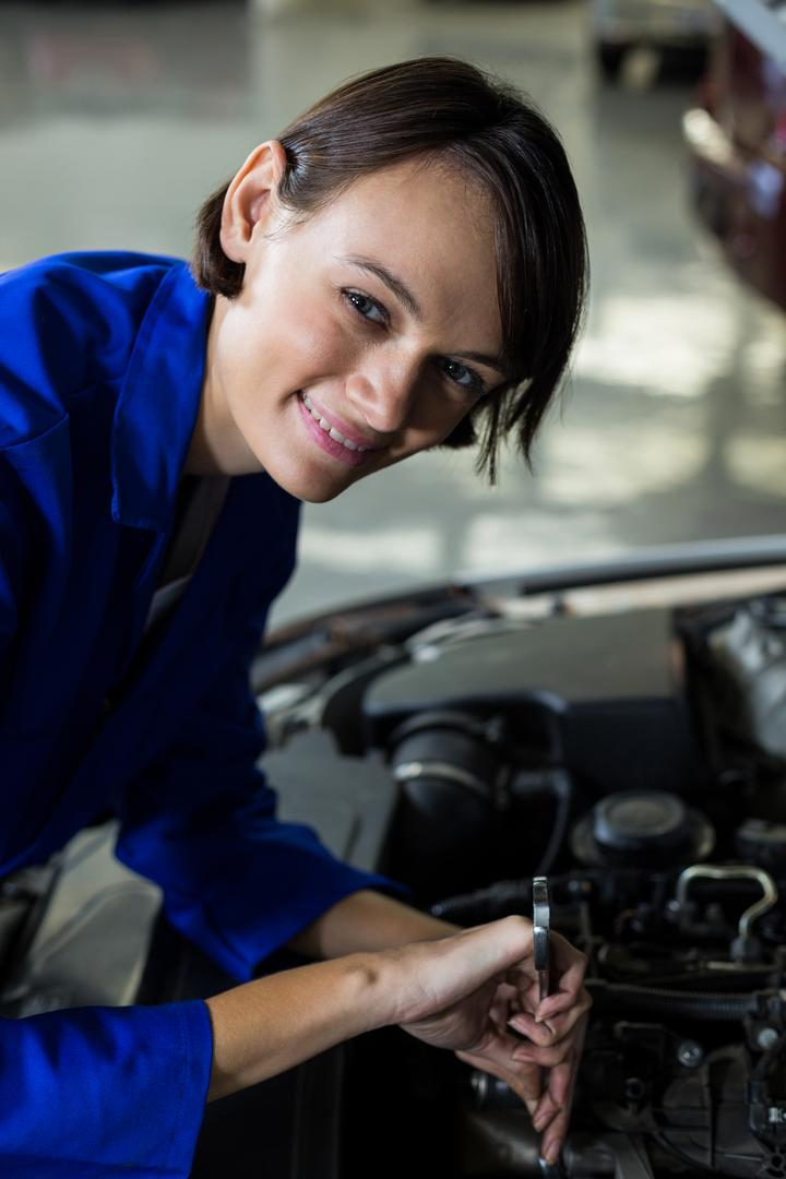 Female mechanic smiling while servicing a car in repair garage