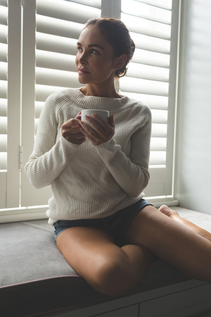 Front view of woman looking away while having a coffee on window seat in a comfortable home