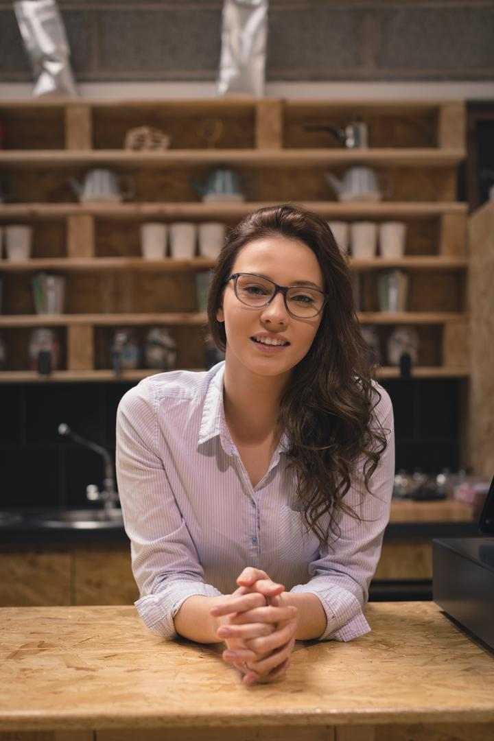 Portrait of smiling beautiful woman standing at counter in café