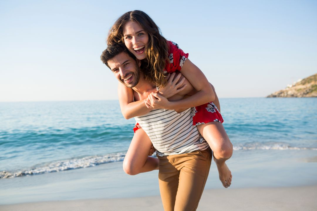 Portrait of young man piggybacking his cheerful girlfriend at beach on sunny day Free Stock Images from PikWizard