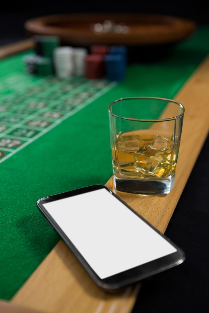 Close-up of mobile phone and whisky glass on roulette table at casino Free Stock Images from PikWizard