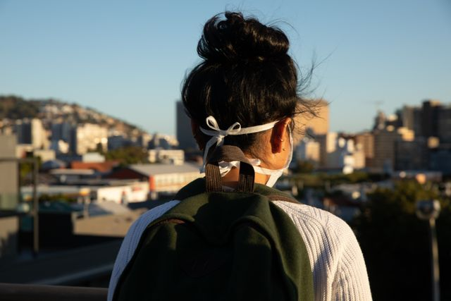 Rear view of woman wearing face mask outdoors