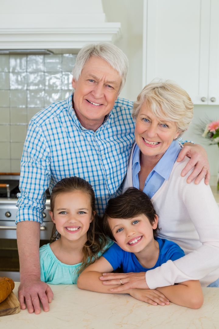 Portrait of happy grandparents and grandchildren standing at kitchen at home