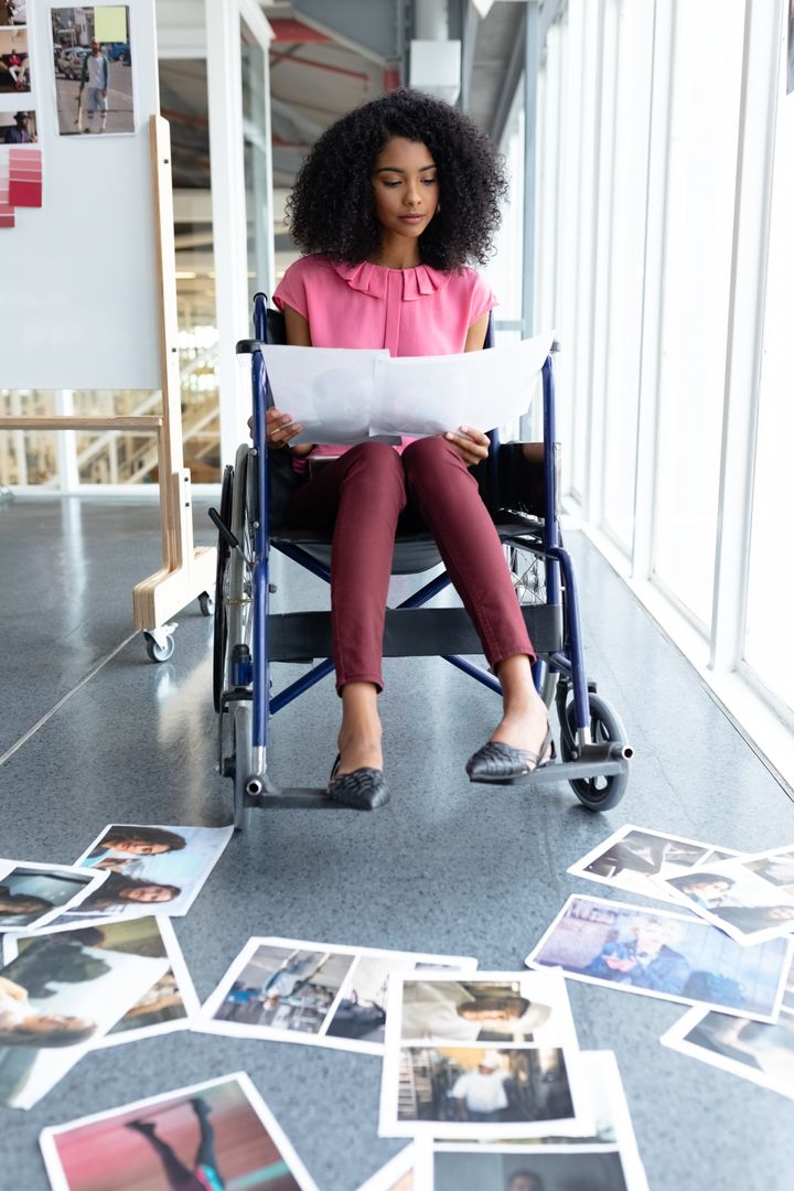 Front view of African american disabled graphic designer looking at photographs in office. This is a casual creative start-up business office for a diverse team