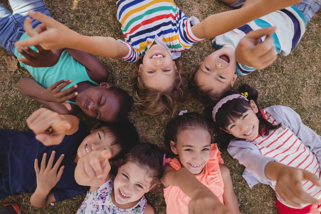 Overhead view of schoolkids lying on grass in park Free Stock Images from PikWizard