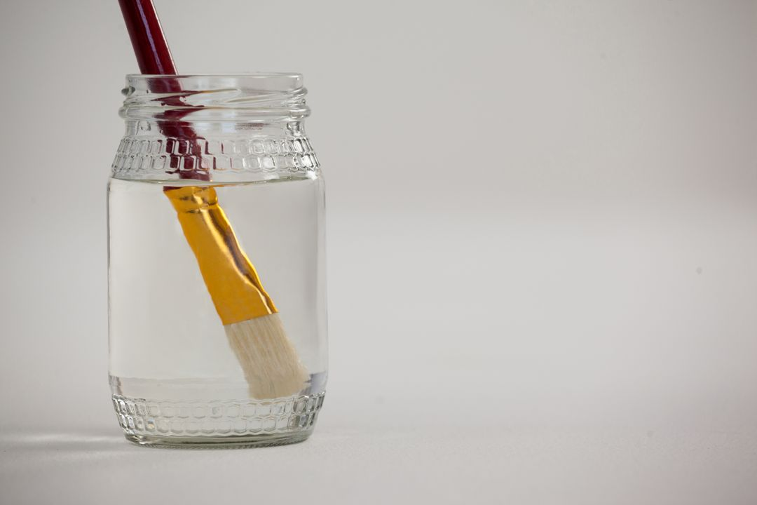 Paint brush in a jar filled with water against white background Free Stock Images from PikWizard