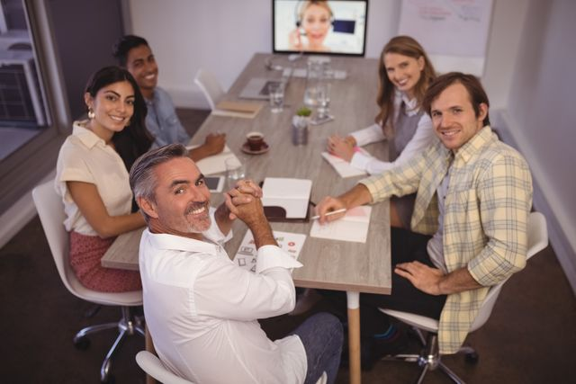 Portrait of smiling business people attending video conference meeting in office