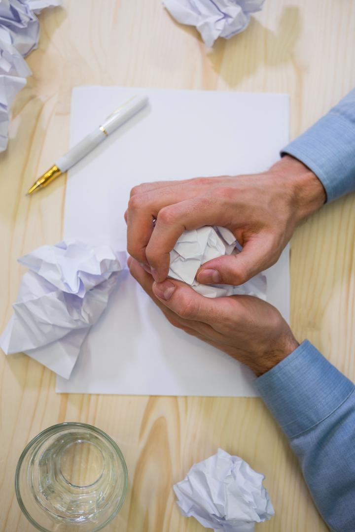 Hands of business executive making paper ball on a desk