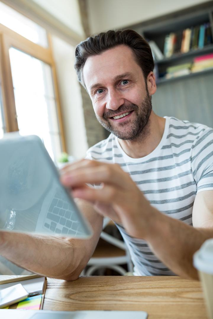 Portrait of smiling man using digital tablet in coffee shop