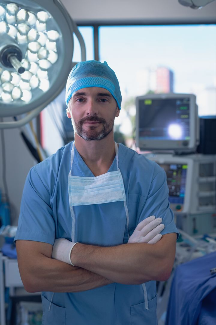 Portrait of male surgeon standing with arms crossed in operating room at hospital