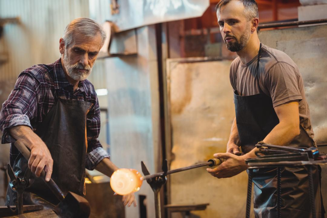 Team of glassblower forming and shaping a molten glass at glassblowing factory