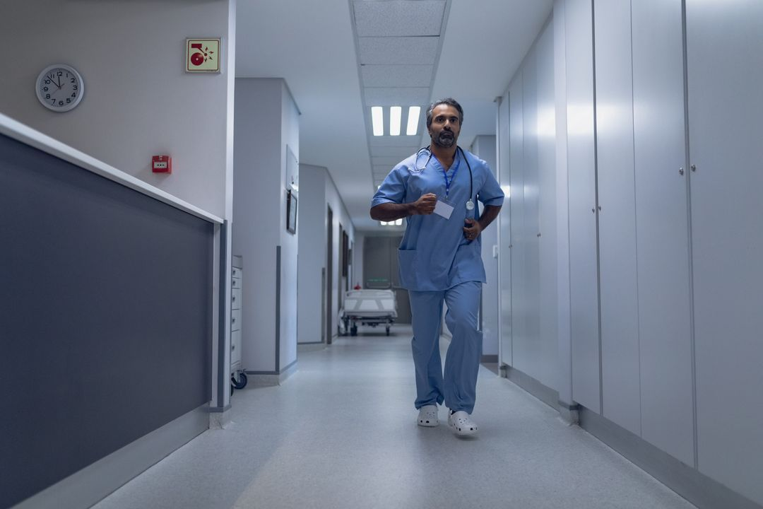 Mature male doctor running in the corridor at hospital