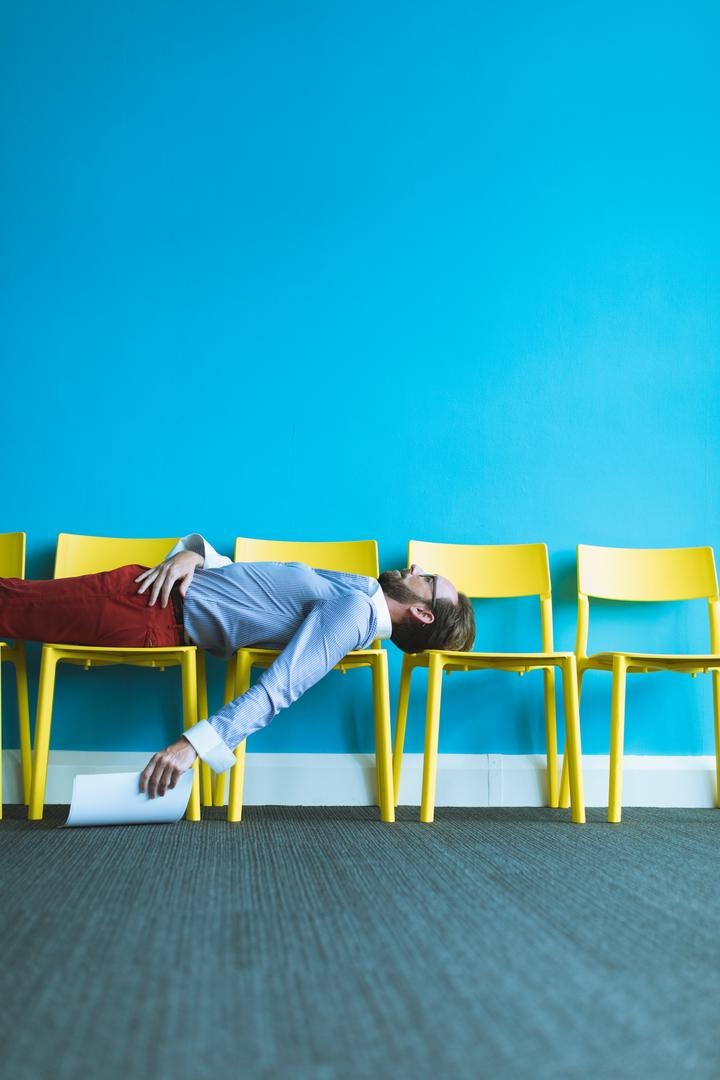 Tired male executive sleeping on chairs in office Free Stock Images from PikWizard