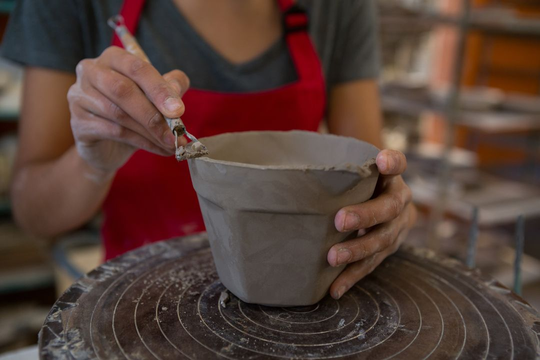 Mid section of female potter molding a mug with hand tool Free Stock Images from PikWizard