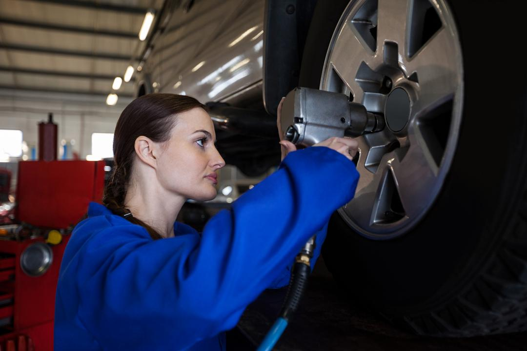 Female mechanic fixing a car wheel with pneumatic wrench at the repair garage Free Stock Images from PikWizard