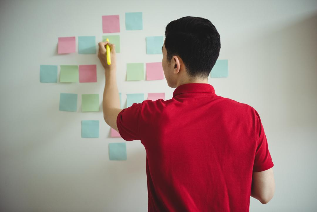 Business executive writing on sticky notes in office Free Stock Images from PikWizard