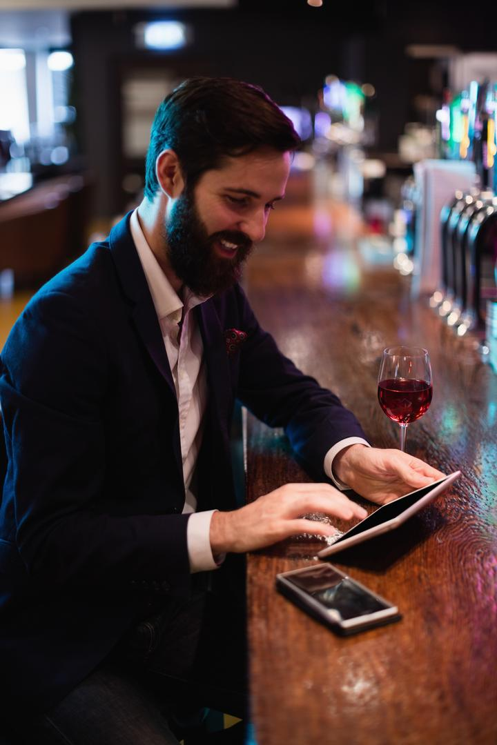 Businessman using digital tablet with wine glass and mobile phone on counter at bar