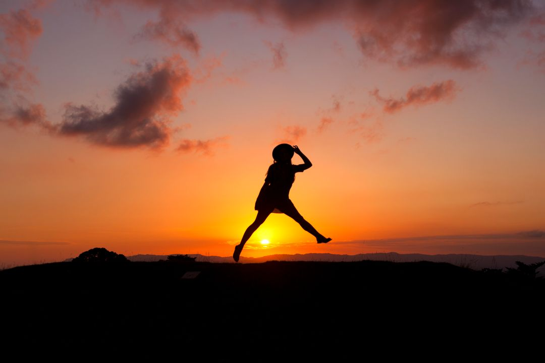 A silhouette of a woman jumping at sunset