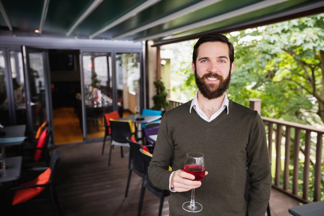 Portrait of smiling man holding glass of wine in bar