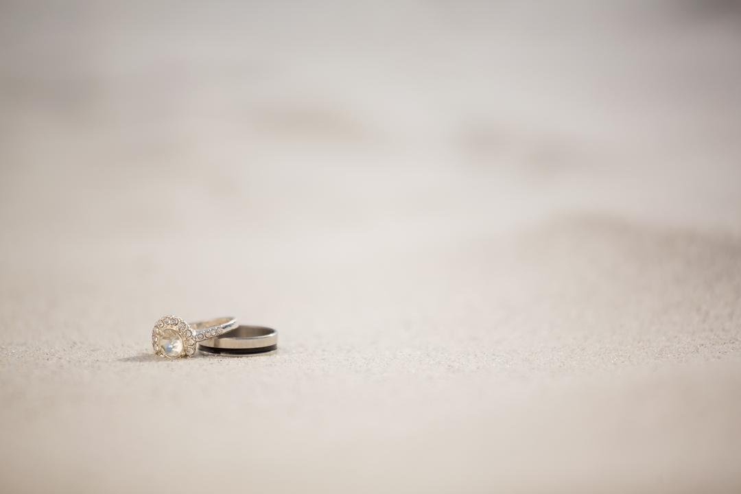 Pair of wedding ring on sand at beach