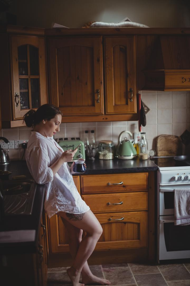 Beautiful woman using mobile phone while having coffee in kitchen at home