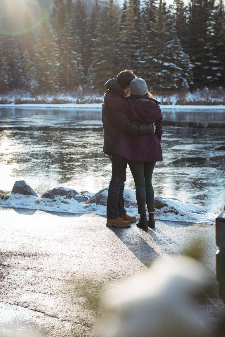 Rear view of romantic couple standing by river in winter